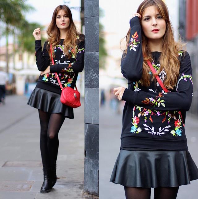 Un look muy chic en el que predomina el color negro con detalles coloridos. Una sudadera con detalles florales combinada con una falda de cuero y botines. El bolso rojo añade mucho color al outfit.