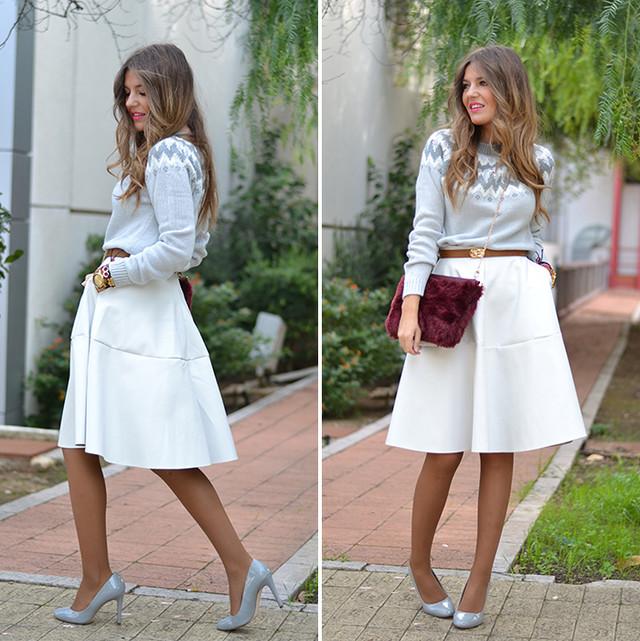 Un look super lady con una falda midi blanca y un suéter gris con cenefas en blanco. Unos salones gris perla y un bolso de piel granate completan este look tan femenino.
