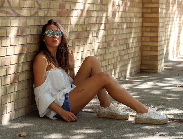 Camiseta blanca con el hombro descubierto con shorts y espadrilles en glitter plateado, de doble suela.