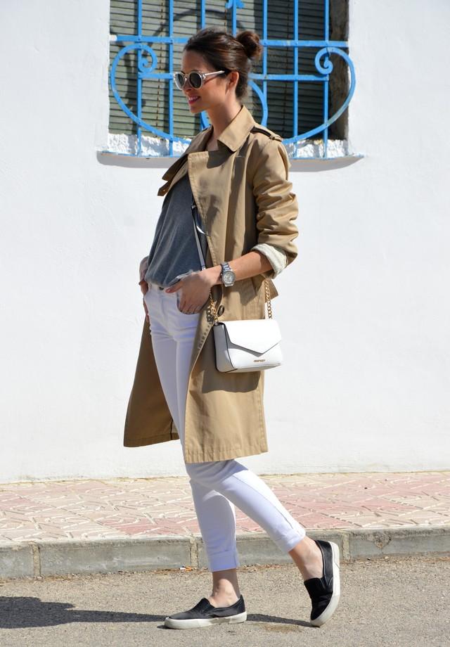 Un look básico en tonos neutros, con jeans blancos, suéter gris y trench beig.