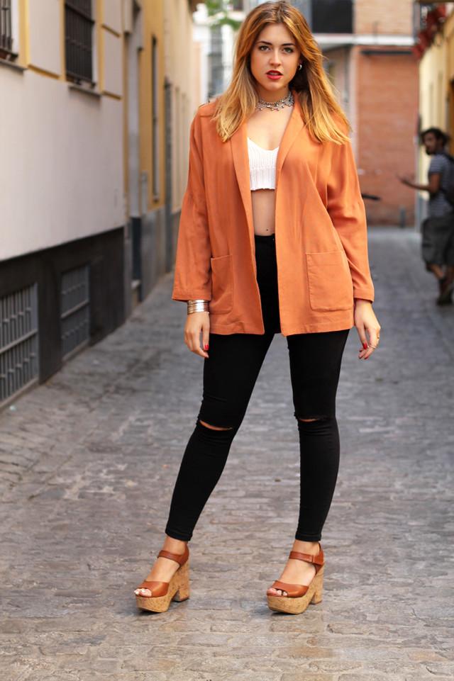 Crop top de croché blanco combinado con unos jeans negros y blazer en naranja oscuro.