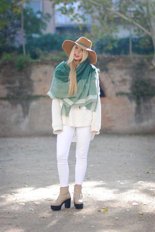 Un outfit lleno de básicos, empezando por unos jeans pitillos blancos, y un jersey oversize, también en blanco. Lo especial de este look son los complementos, como esta maxi bufanda en tonos verdes y el sombrero marrón. Los botines beige también le dan un toque todoterreno al conjunto.