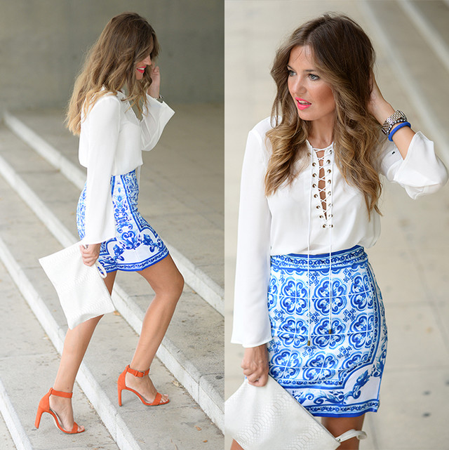 Vintage skirt printed in blue tones combined with a white blouse and orange sandals.